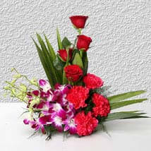 Inspiration - Basket arrangement of 4 purple orchids, 4 pink carnations and 4 red roses.